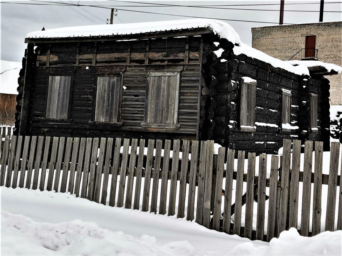 На сгоревшем доме видно, что он построен из бревен и обшит досками.